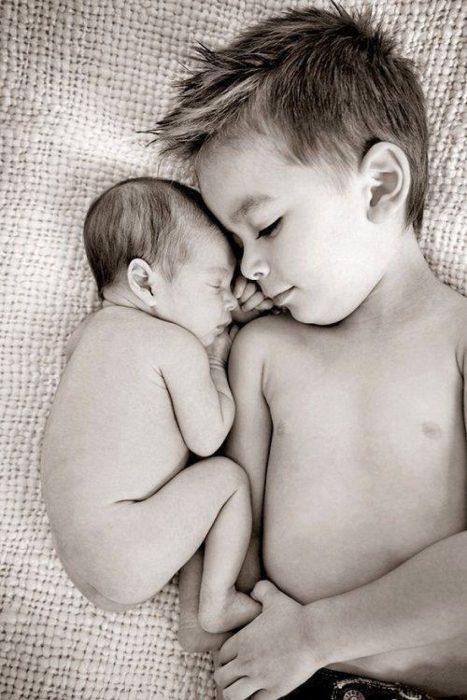 Niño y su hermano recien nacido acostados en una cama