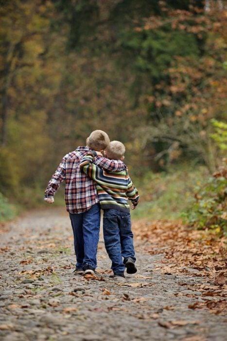 Hermanos abrazados mientras caminan por en medio de un bosque