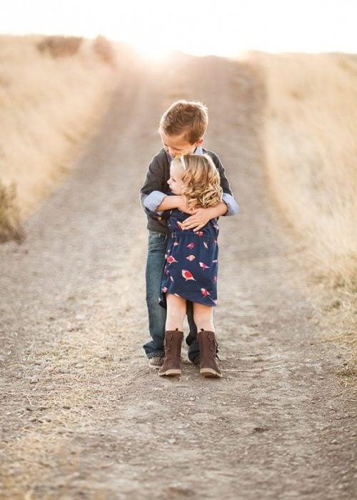 Niña y su hermano abrazados en medio del desierto