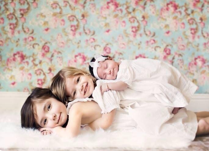 Hermanas recostadas una sobre la otra mientras están recostadas en la cama