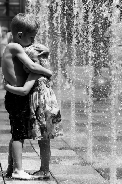 Niños abrazados mientras están bajo el chorro de una fuente