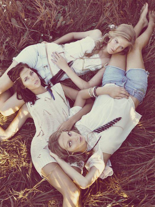 tres hermanas recostadas en el pasto mientras les toman una fotografía