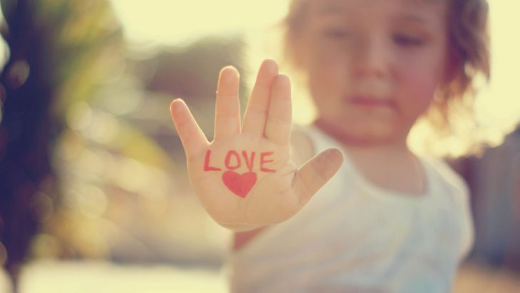 niña con mano extendida y corazon pintado love