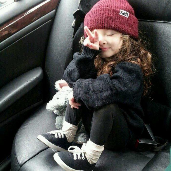 niña con gorra sentada señal amor y paz