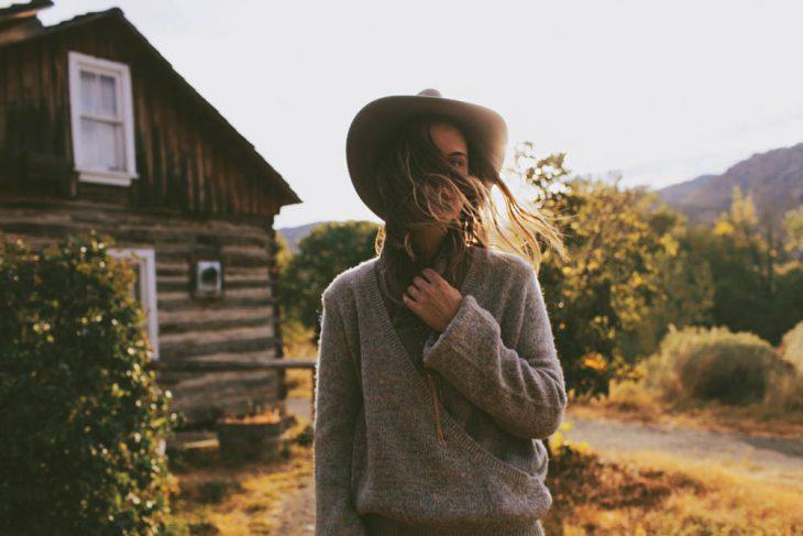 mujer con sombrero afuera de cabaña sonrie