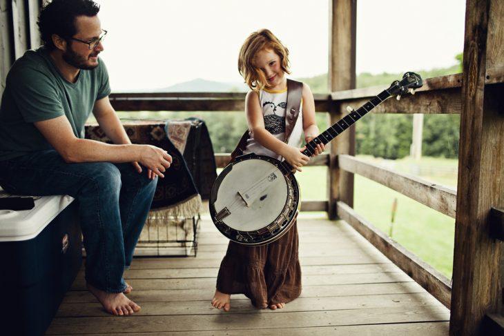 padre con hija tocando guitarra sonrien