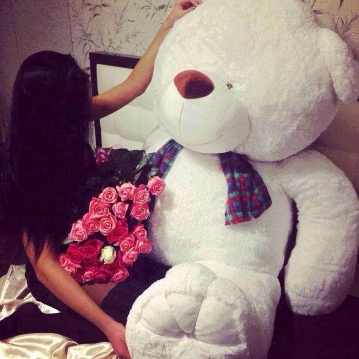 chica con oso de peluche gigante y flores