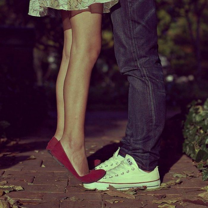 chica bajita se sube a los zapatos de su novio para besarlo