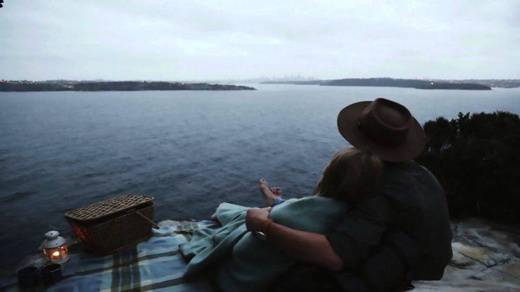 pareja abrazandose a lado de un lago