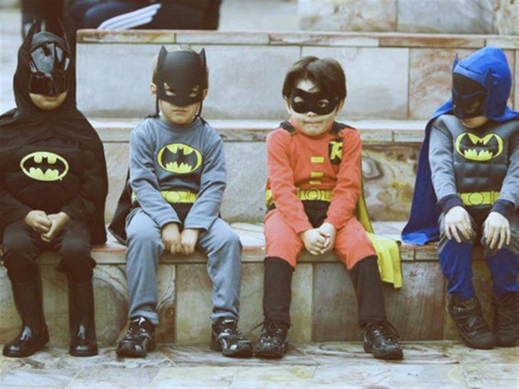 niños sentados amigos vestidos de super heroes
