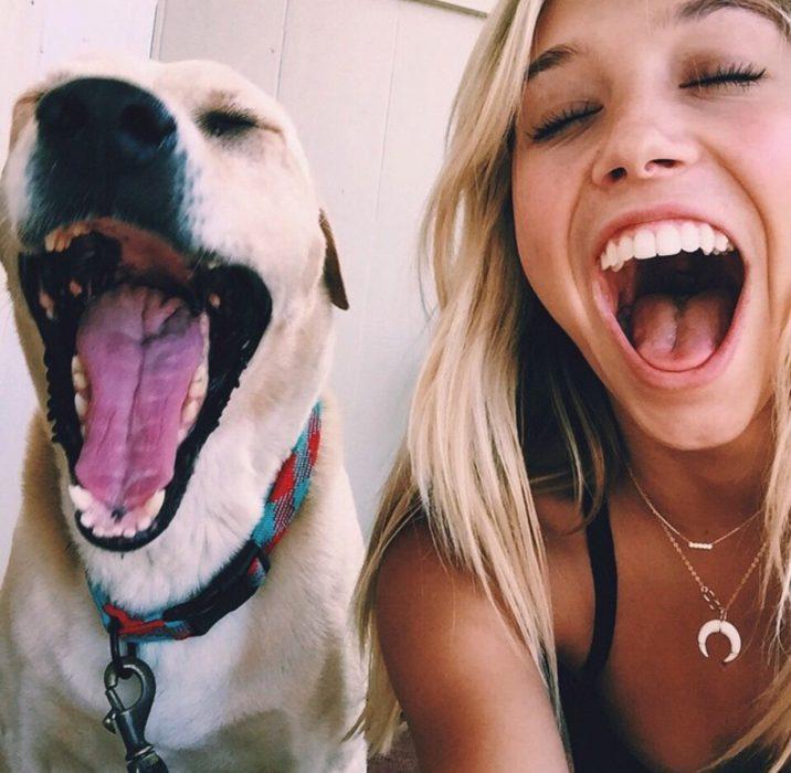chica sonriendo con perro abriendo la boca feliz