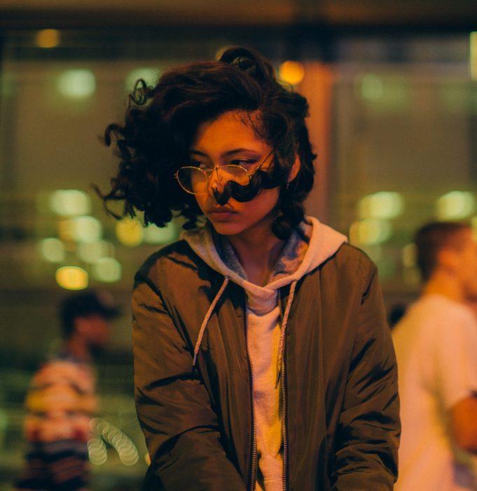mujer lentes cabello rizado calle noche