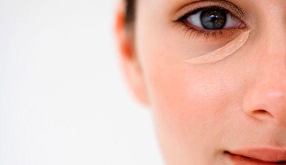 Mujer aplicándose corrector de ojos bajo las pestañas inferiores