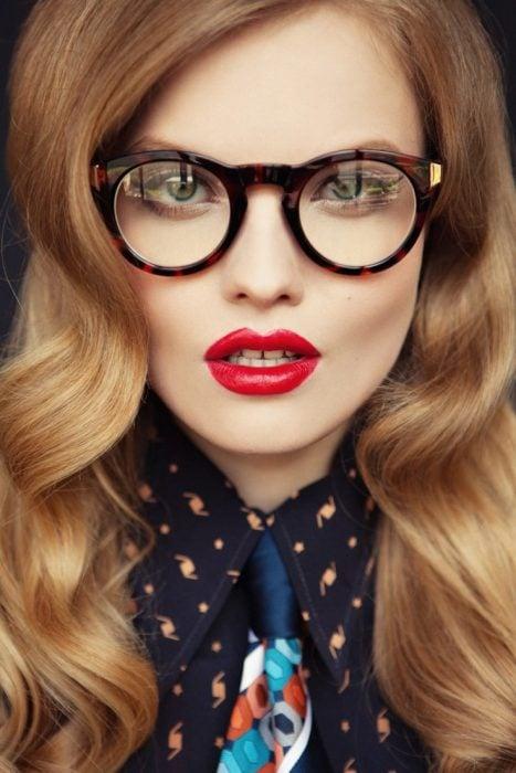 Chica usando lentes mientras tiene los labios pintados de rojo