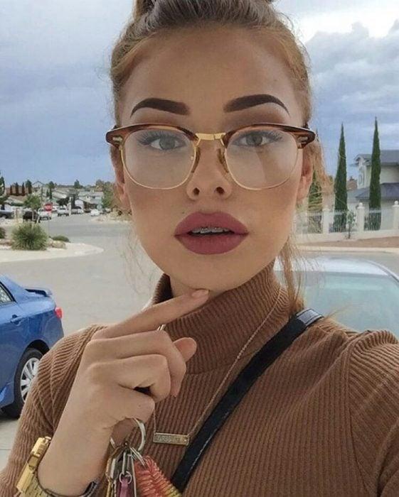 Chica usando lentes y resaltando sus cejas
