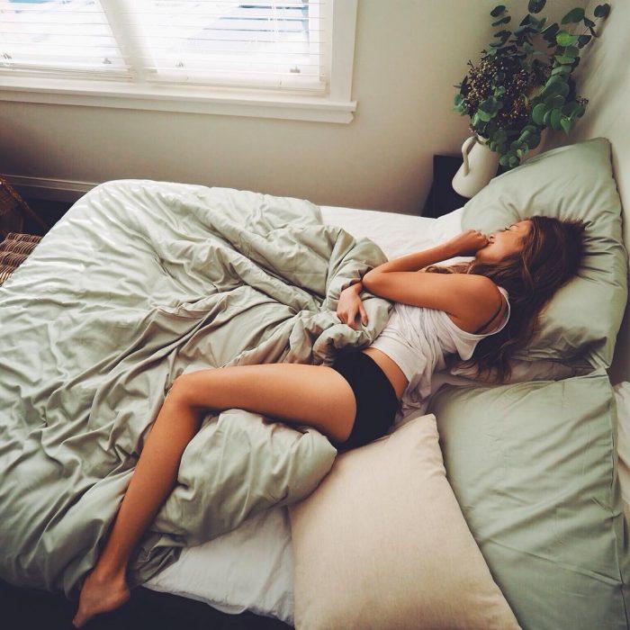 mujer acostada con problemas para dormir