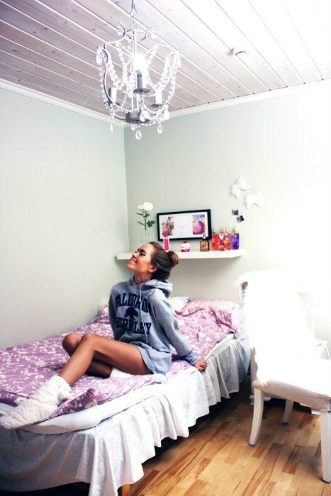 Chica en su cuarto sonriendo