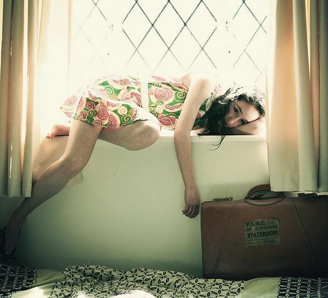 Chica recostada sobre una ventana junto a una maleta