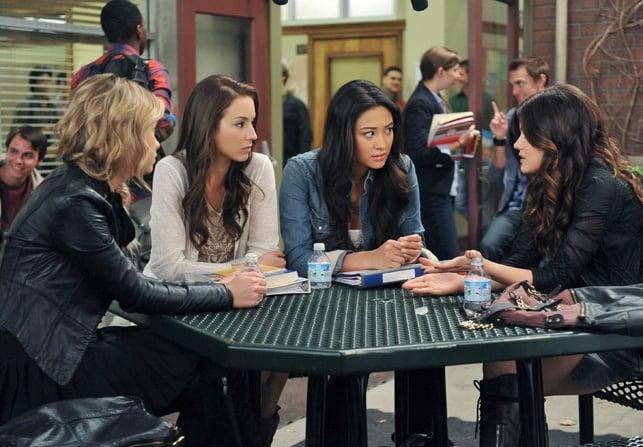 Escena de la serie pretty little liars chicas sentadas en el comedor de una escuela hablando