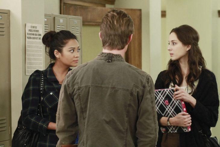 Escena de la serie pretty little liars chicas hablando con un chico en le pasillo