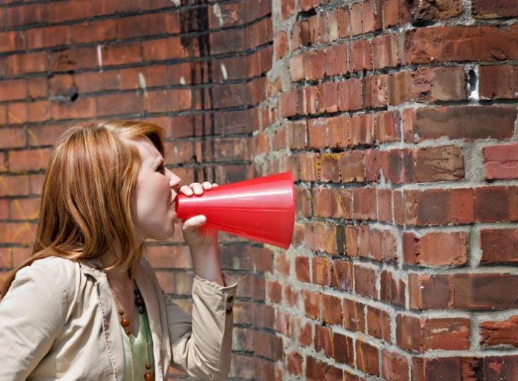 mujer hablando a un muro