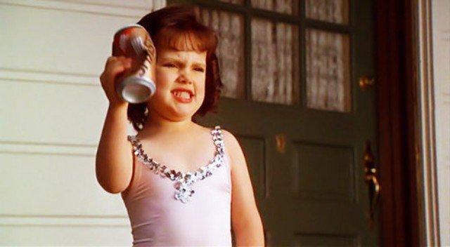 niña aplastando lata de refresco