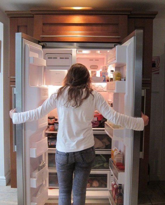 chica con refrigerador abierto