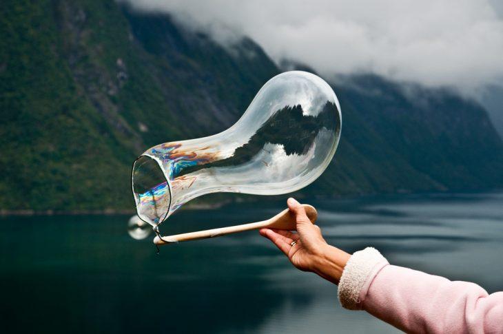 mujer haciendo burbuja de jabón