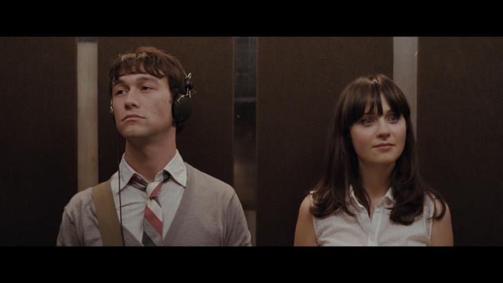 mujer y hombre en un elevador el escuchando musica