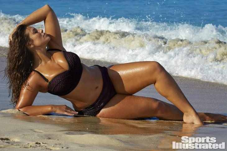 MOdelo Asheley Graham sentada sobre la playa posando para la revista Sports Illustrated