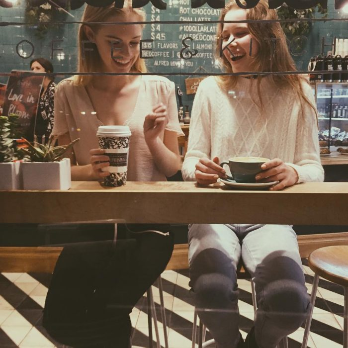 Chicas platicando mientras beben café