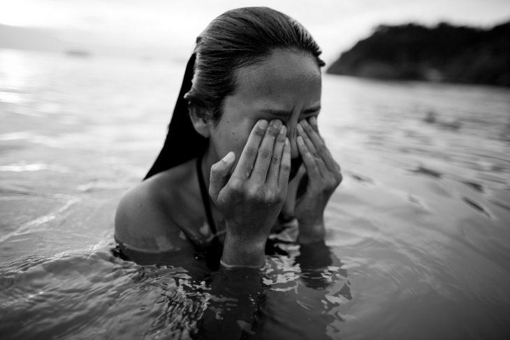 Chica en el agua tallando los ojos