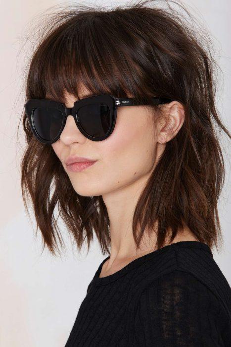 Chica con un corte bob y fleco usando lentes
