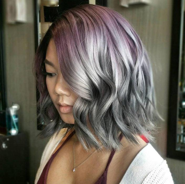 Chica con un corte bob teñido en color gris con la raíz morada