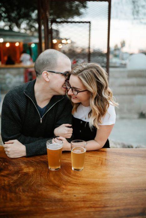 Pareja en un bar tomando una cerveza y conversando