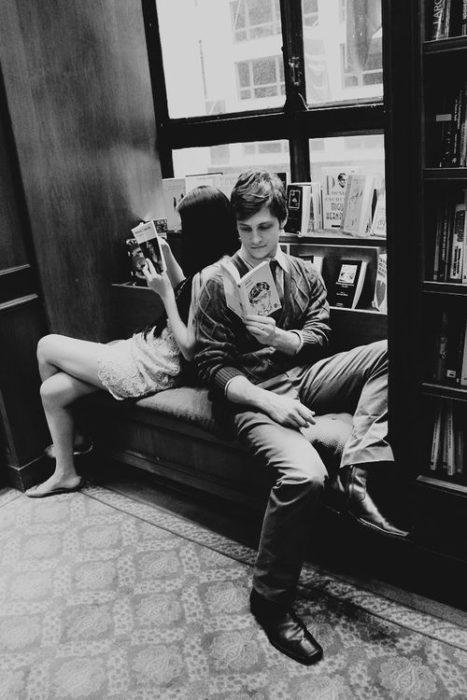 Pareja de novios en una biblioteca leyendo juntos un libro mientras están sentados en un sofá