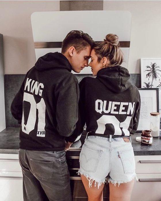 Pareja de novios usando sudaderas que dicen king y queen