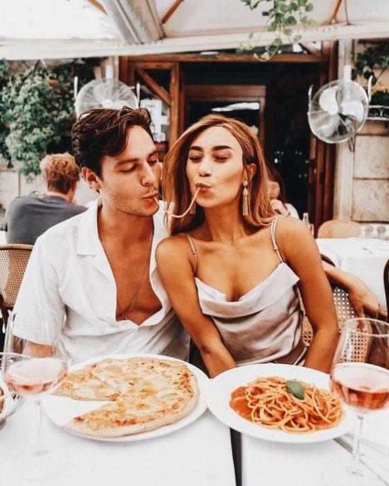 Pareja de novios en un restaurante comiendo pizza y spaguetti