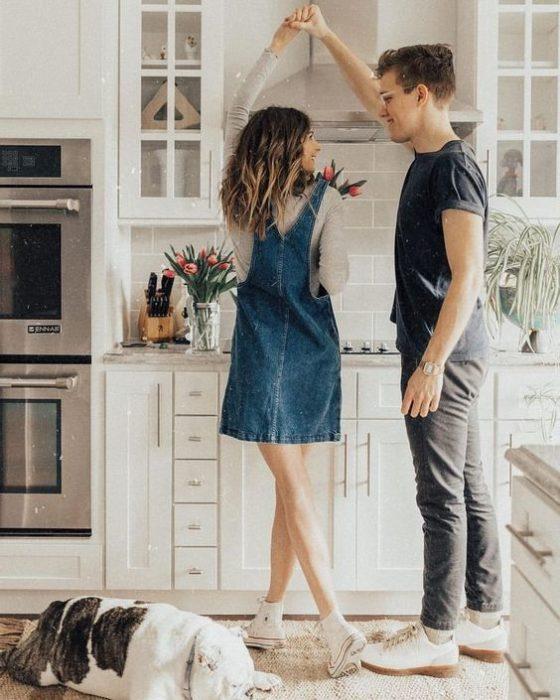 Pareja de novios bailando en la cocina de su casa