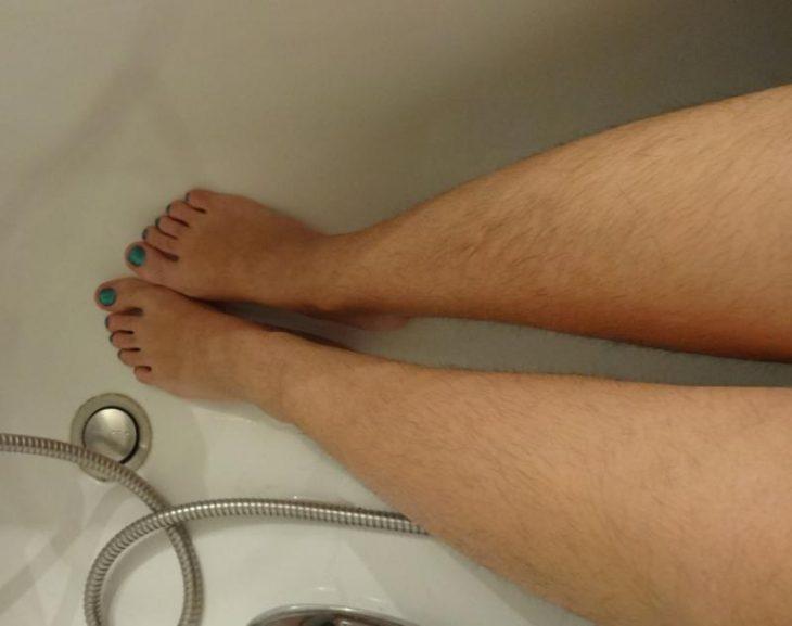 Chica con las piernas no depiladas mientras está en la bañera