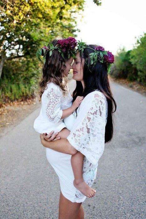 Mujer embarazada sosteniendo a una niña en brazos