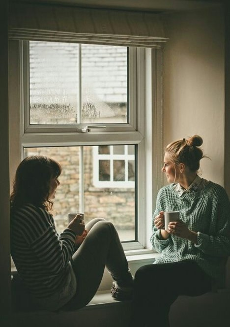 Chicas sentadas en una ventana mientras toman café