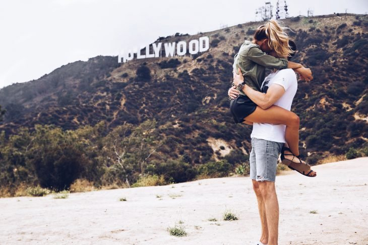 Pareja de novios besándose frente al letrero de Hollywood