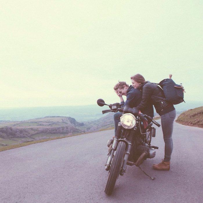 Pareja de novios parados sobre una motocicleta a un lado de la carretera