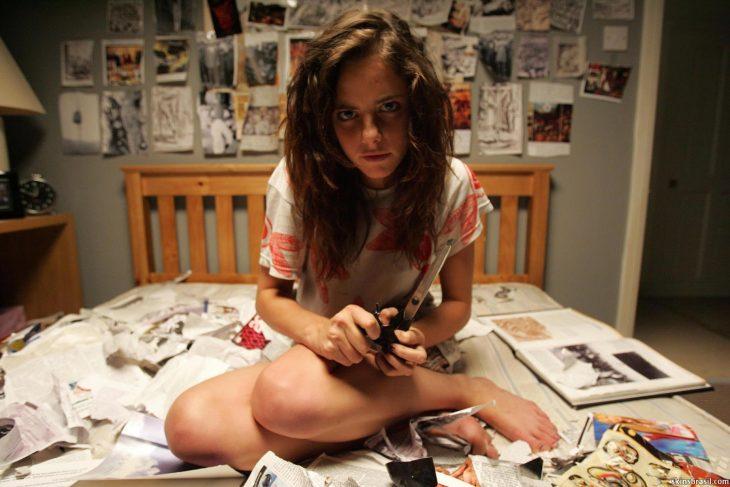 Chica sentada en la cama con el rostro molesto