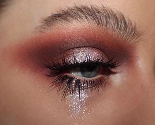 Chica con el maquillaje de ojos esparcido por toda la cara