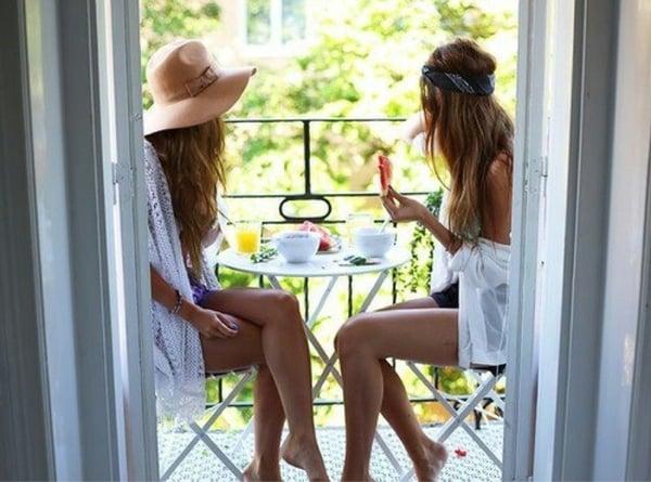 Chicas sentadas en la terraza de una casa comiendo el desayuno
