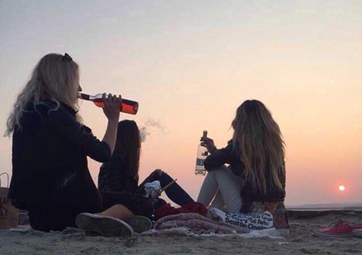 Chicas bebiendo en la playa