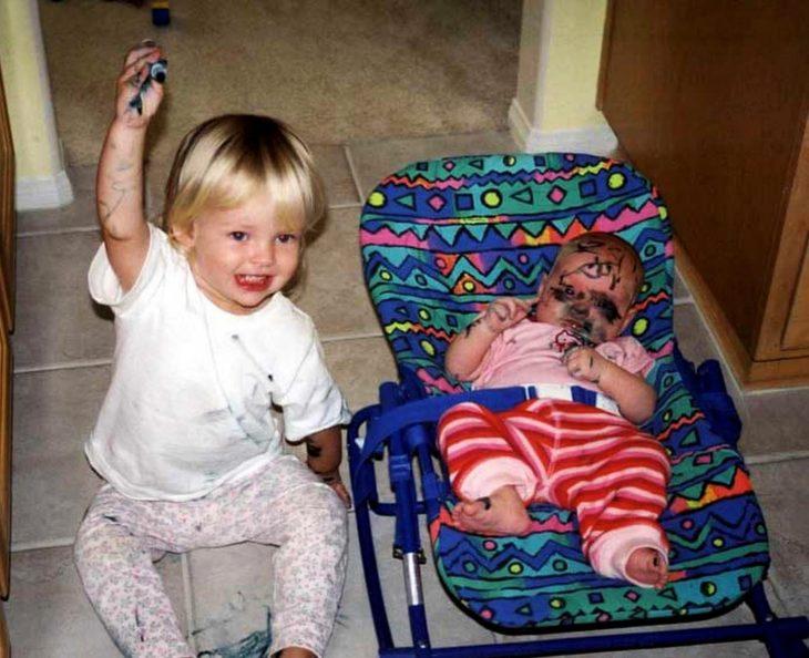 Niño travieso pintando a su hermanito