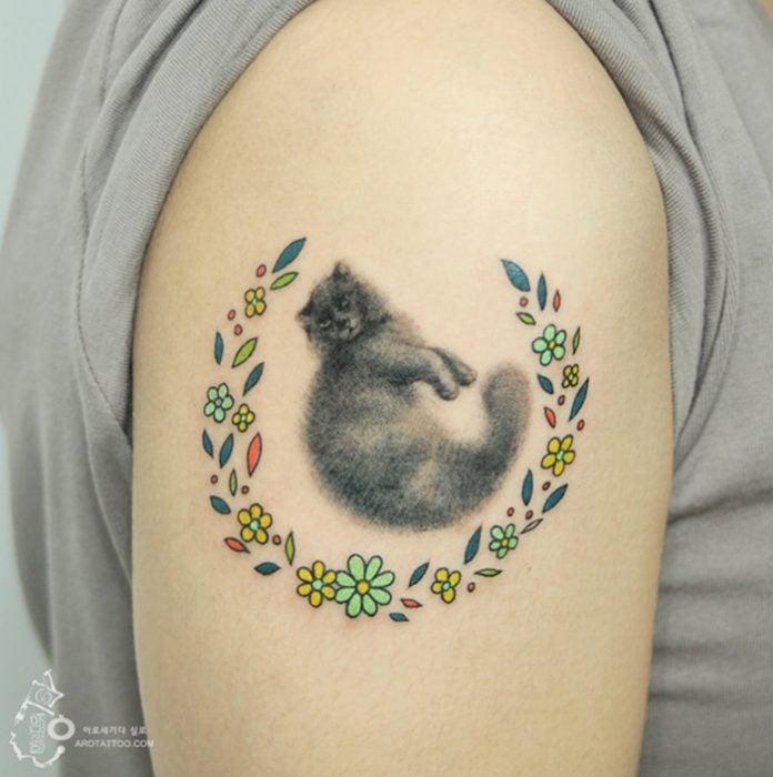 Tatuaje de acuarela en forma de gato colocado en el brazo